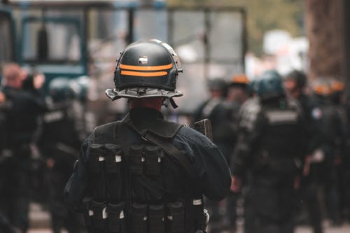 Back view of anonymous policeman in helmet and bulletproof vest maintaining law and order while standing on city street