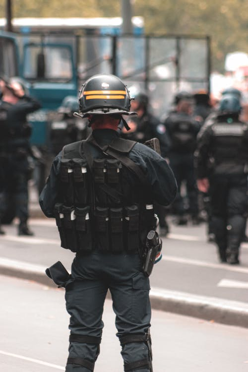Back view of armed police officer wearing uniform with helmet and body armor performing duties while standing on road