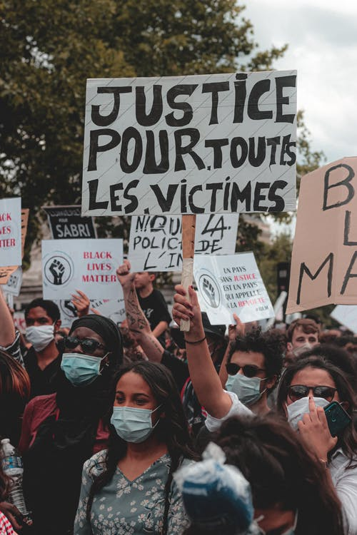 Protesting people in masks standing on street