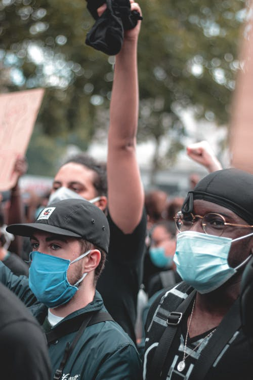 Group of diverse young people in casual clothes with protective masks standing on protest during pandemic