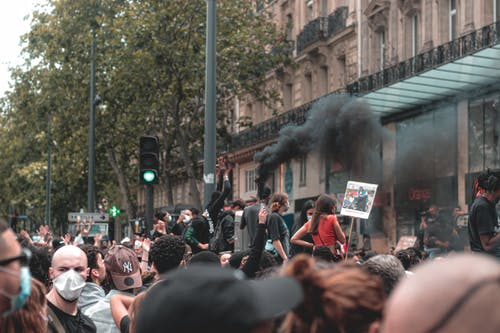 Anonymous ethnic crowd of people standing on city street with posters and smoke bomb in protest against racism