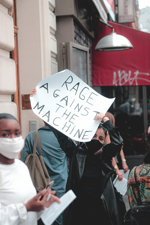 Anonymous female in protective mask participating in demonstration and holding placard saying Rage against the machine