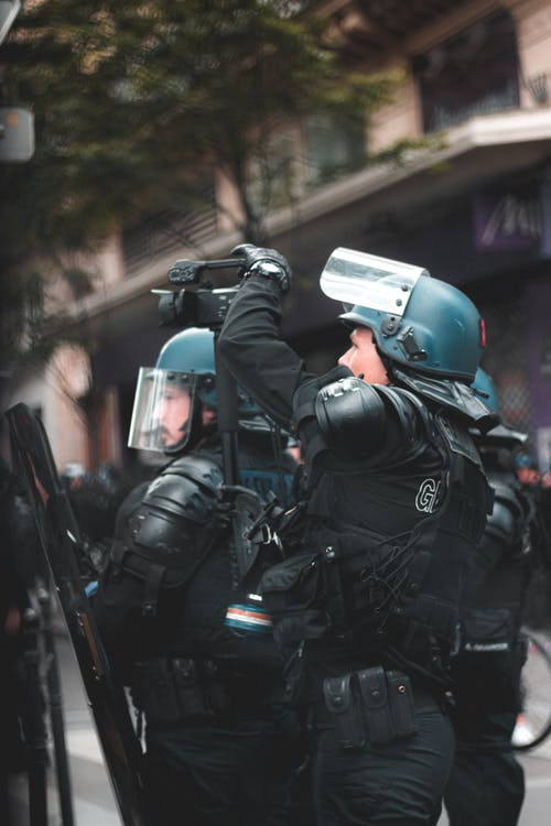 Unrecognizable police officer in protective helmet on street