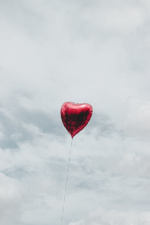 From below of red balloon in shape of heart flying in cloudy sky