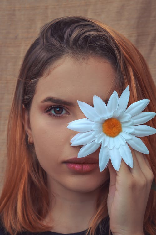 Thoughtful woman covering face with flower