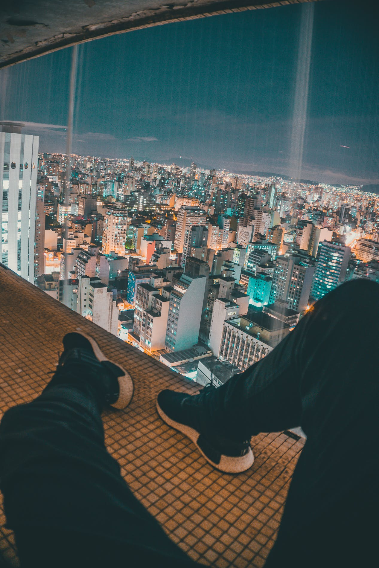 Man Sitting on Top of Building Near Glass Window Viewing Cityscape