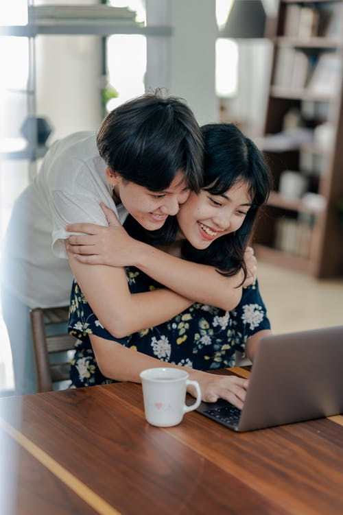 Photo of Couple Smiling While Looking at Laptop