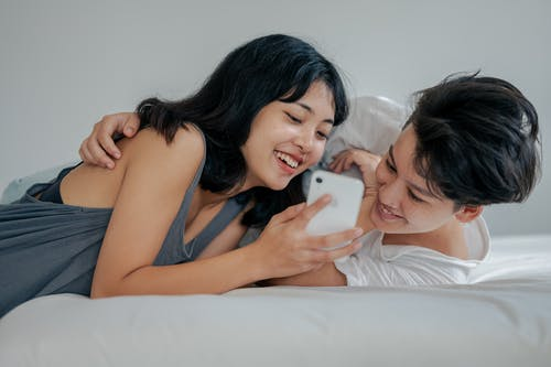 Photo of Couple Lying on Bed While Using Smartphone