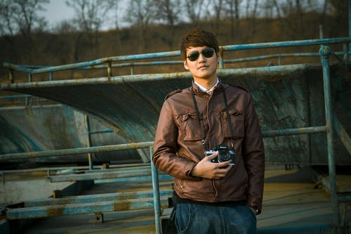 Man in Brown Leather Jacket Wearing Black Framed Sunglasses Holding Black Dslr Camera Standing in Front of Black Steel Bar during Daytime