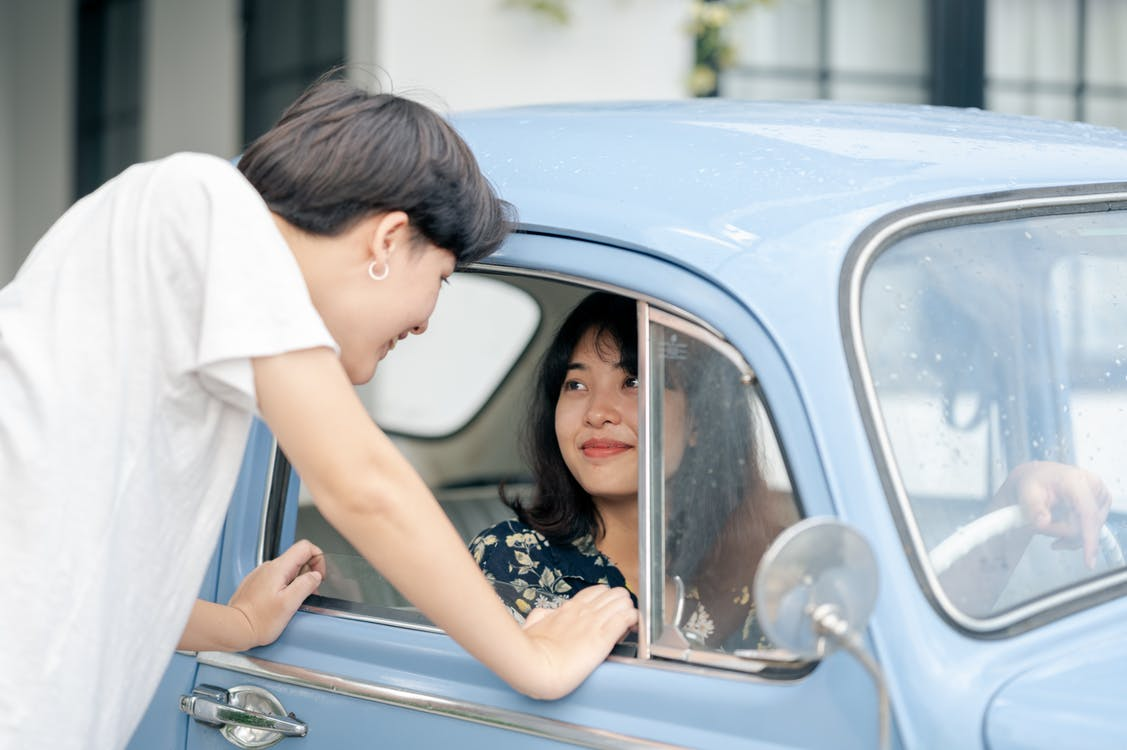 Photo of Woman Inside the Car While Looking at Her Boyfriend