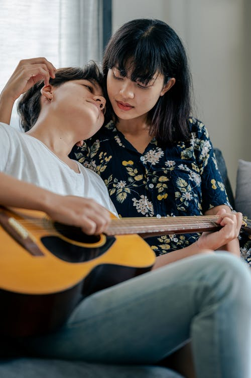 Photo of Man Playing Acoustic Guitar With Her Woman