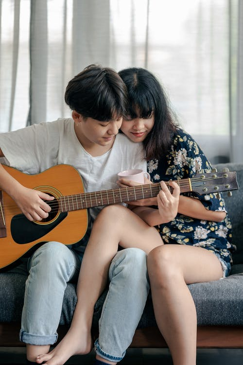 Photo of Man in White Shirt Playing Acoustic Guitar With Her Woman