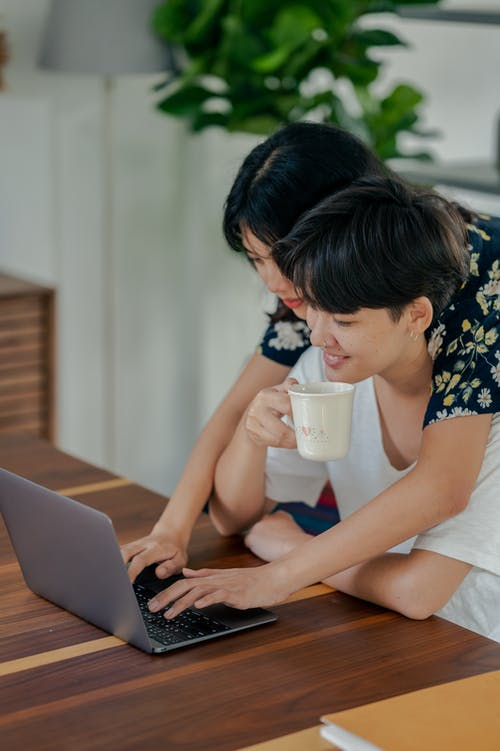 Photo of Couple Looking at Laptop