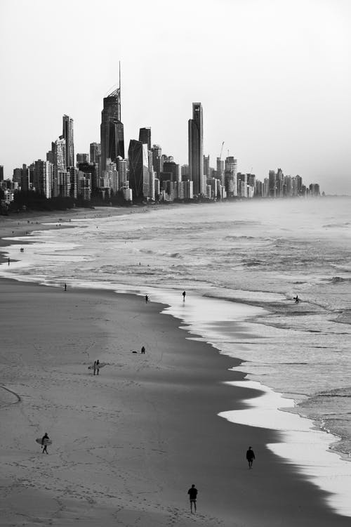 Grayscale Photo of People on Beach Against City Skyline