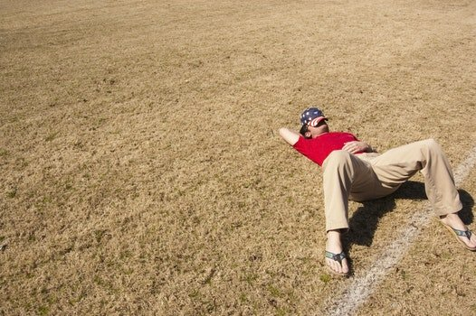 Men in Red Shirt Lying on a Brown Ground during Daytime