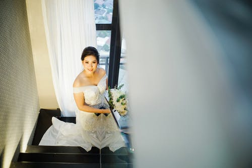 High Angle Photo of Woman in White Wedding Gown Holding Bouquet of Flowers