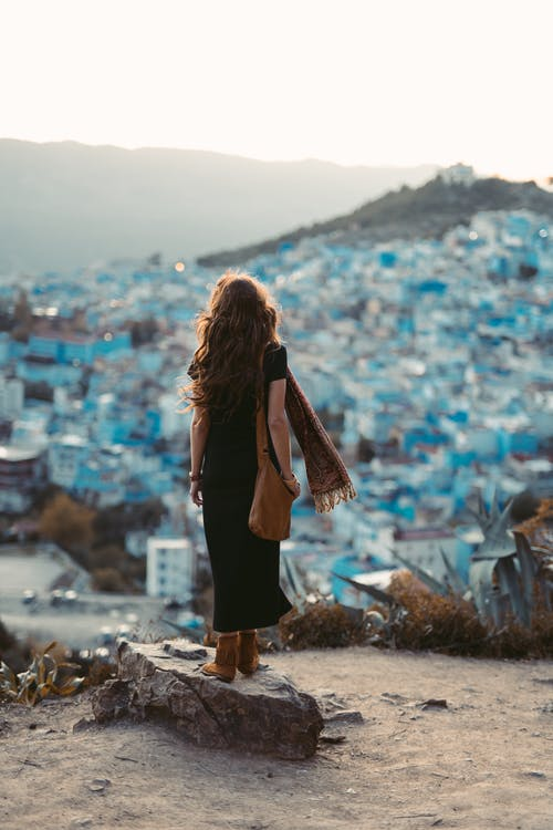Woman in Black Dress Standing on Brown Rock