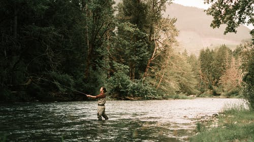Man Standing on River While Fishing