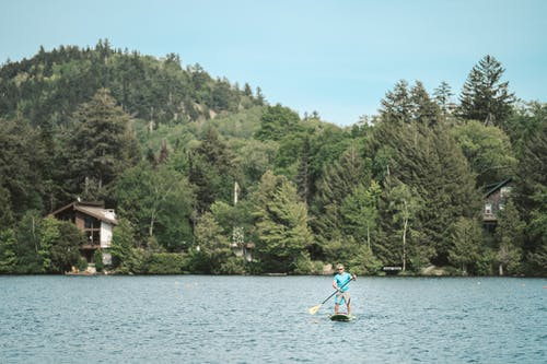 Photo of Man in Blue Shirt Paddleboarding