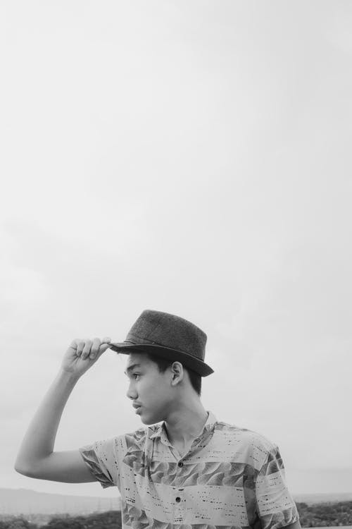 Grayscale Photo of Man Wearing Fedora Hat
