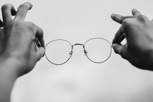 Person Holding Silver Framed Eyeglasses