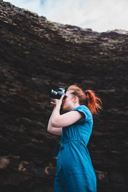 Woman in Blue Sleeveless Dress Taking Photo Using Black Dslr Camera