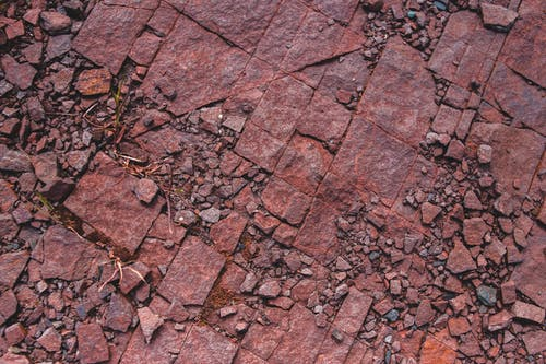 Overhead view of old dark red sharp masonry debris and small stones with dry grass on ground in daylight