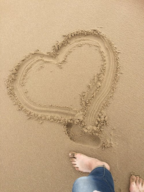 Person Standing on Brown Sand With Heart Shaped Sand