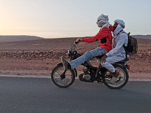 Two Men Riding Motorcycle on Road