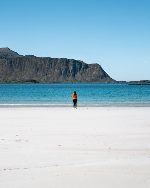 Photo of Person Standing on White Sand Beach