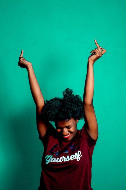 Cheerful black woman showing fuck gesture