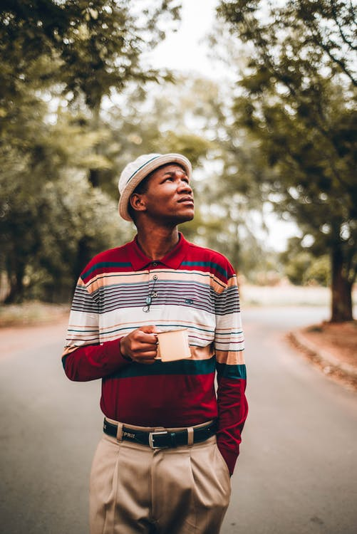 Serious black man in stylish outfit with cup in park