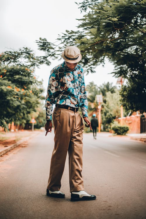 Man in Blue Red and White Long Sleeve Shirt and Brown Pants Standing on Road during