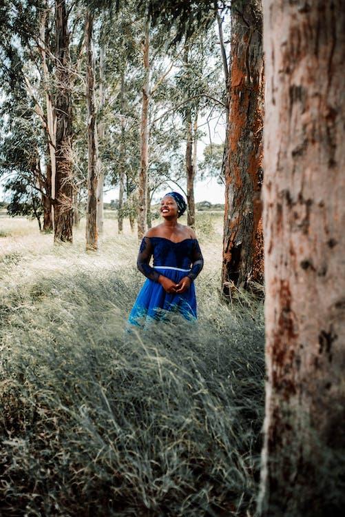 Woman in Blue Dress Sitting on Brown Grass Field