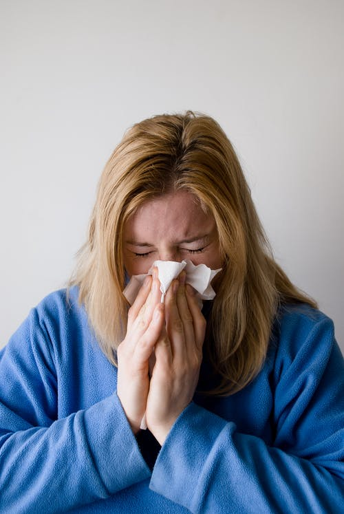 Sick Woman Wiping Her Nose with Tissue