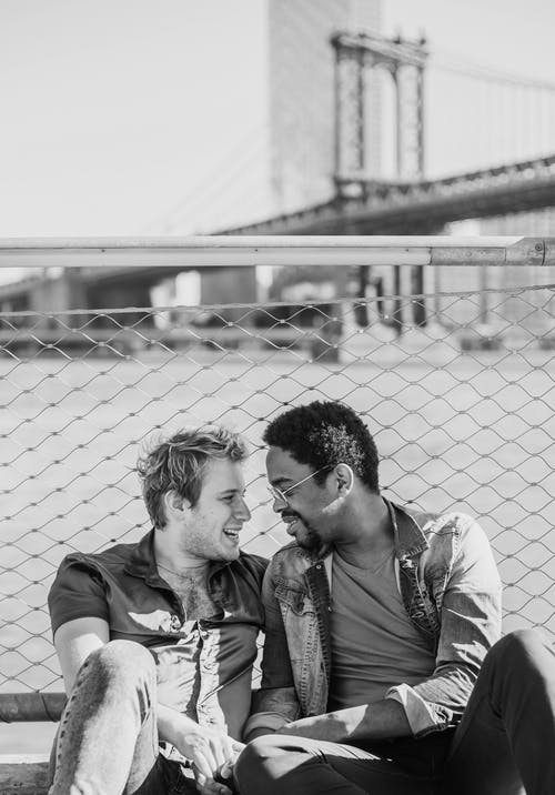 Grayscale Photo of Two Men Sitting and Looking at Each Other