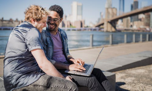Two Men Sitting Outside With a Laptop