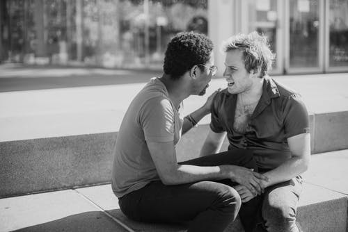 Grayscale Photo of Two Men Talking