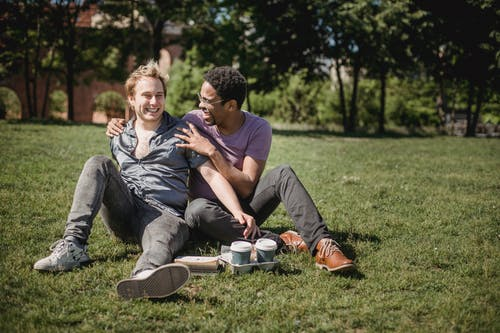 Two Men Sitting on the Grass and Being Affectionate