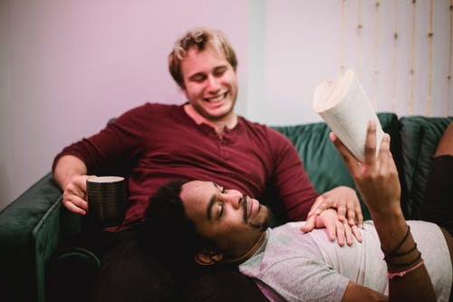 Man Resting his Head on Another Man's Legs and Reading a Book