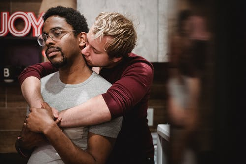 Man Hugging Another Man from Behind