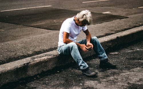 Man in White T-shirt and Blue Denim Jeans Sitting on Road