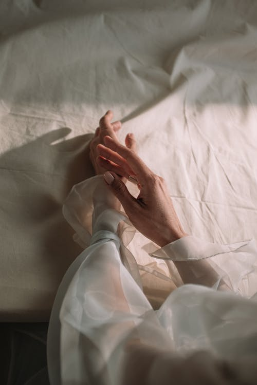 Person in White Dress Shirt Lying on Bed