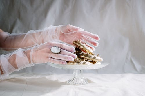 Person Holding Gold and Silver Round Coins