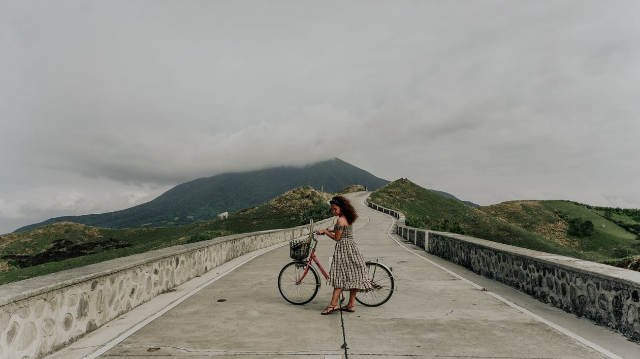 Woman in White and Black Dress Riding on Bicycle on Gray Concrete Bridge