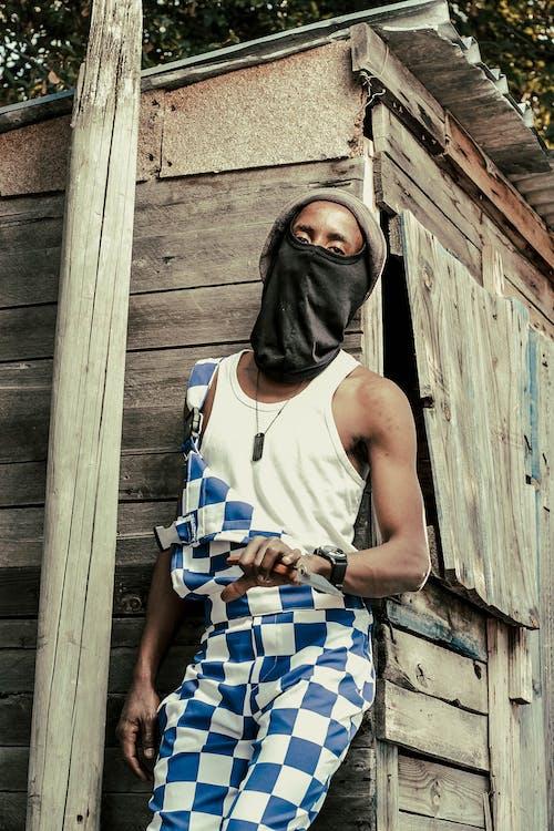 Black man in mask near wooden building