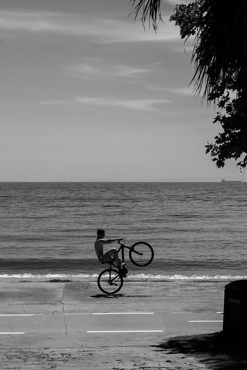Grayscale Photo of Man Riding Bicycle on Beach