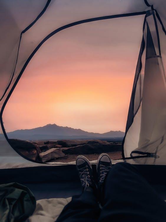 Traveler lying in tent and enjoying bright sunset light