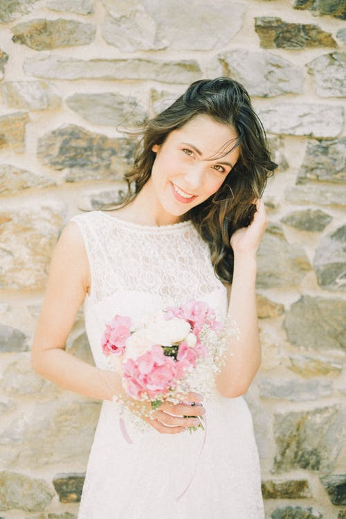 Woman in White Floral Sleeveless Dress Holding Pink Rose Bouquet