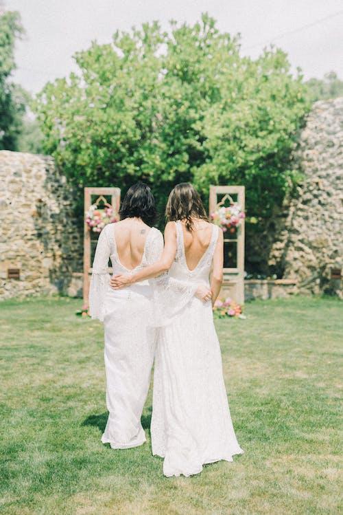 Photo of Women in White Wedding Dress Walking on Grass